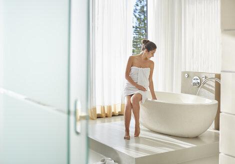 Woman wrapped in towel preparing a bath - HOXF00055