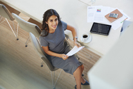 Portrait smiling businesswoman reviewing paperwork and drinking coffee at conference table - HOXF00061