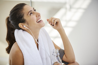 Laughing woman listening to music with headphones resting post workout - HOXF00064