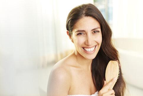 Portrait smiling brunette woman brushing hair - HOXF00073