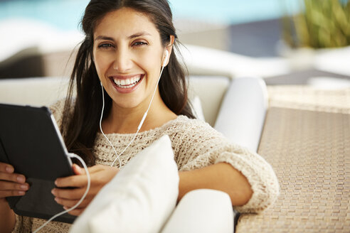 Portrait smiling woman using digital tablet and headphones on sofa - HOXF00106