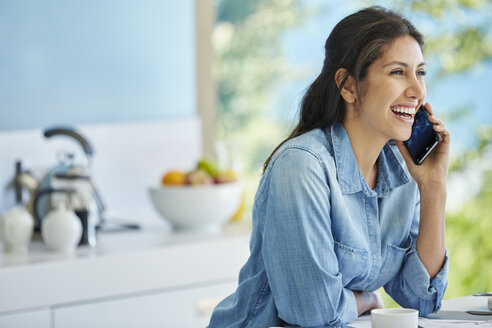 Smiling woman talking on cell phone in kitchen - HOXF00121
