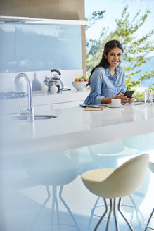 Portrait smiling woman using cell phone at kitchen counter - HOXF00124