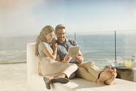 Couple relaxing using digital tablet on sunny luxury balcony with ocean view - HOXF00133