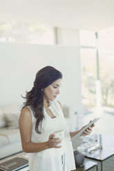 Serious woman drinking coffee using digital tablet in living room - HOXF00136