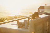 Silhouette couple using cell phone on chaise lounge with sunset ocean view - HOXF00139