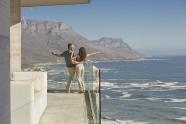 Carefree couple standing on sunny luxury balcony with ocean and mountain view - HOXF00145