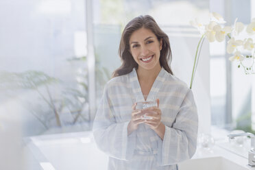 Portrait smiling brunette woman in bathrobe drinking water - HOXF00148