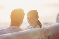 Smiling couple talking on sunset balcony - HOXF00151