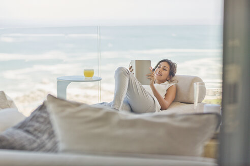 Woman relaxing reading book on chaise lounge on luxury balcony with ocean vie - HOXF00154