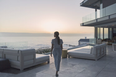 Woman walking on luxury home showcase exterior patio at sunset - HOXF00157