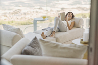 Smiling woman reading book relaxing on chaise lounge - HOXF00160