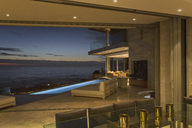 Illuminated home showcase patio with lap pool and twilight ocean view - HOXF00166
