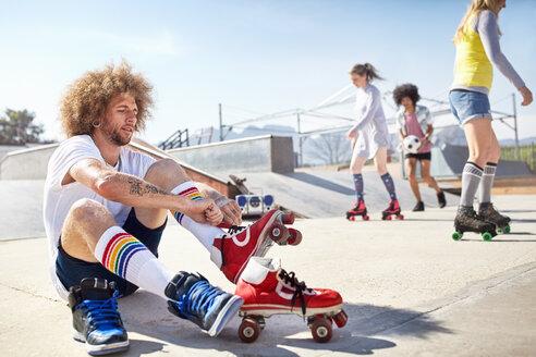 Man putting on roller skates at sunny skate park - CAIF04198