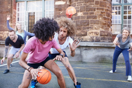 Friends playing basketball on urban basketball court - CAIF04210