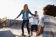 Boyfriend helping girlfriend on skateboard in sunny skate park - CAIF04213