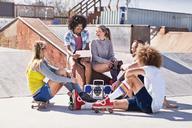 Friends in roller skates and on skateboard using digital tablet at sunny skate park - CAIF04240
