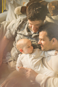 Affectionate male gay parents and son cuddling - CAIF04285