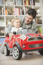 Father pushing baby son in toy car - CAIF04294