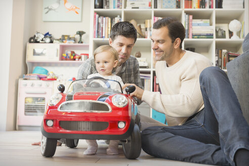 Male gay parents and baby son playing with toy car - CAIF04312