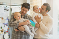 Male gay parents holding baby sons in kitchen - CAIF04327