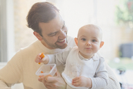 Portrait smiling, cute baby son and father eating carrots - CAIF04336