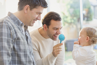 Male gay parents and baby son playing with rattle - CAIF04345
