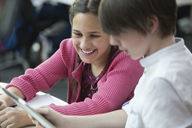 Smiling students using digital tablet in classroom - CAIF04384