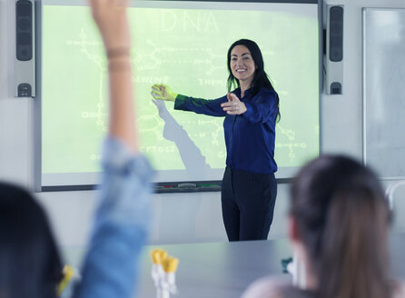 Smiling female science teacher leading lesson at projection screen in classroom - CAIF04402