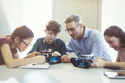 Male teacher helping students assembling robotics in classroom - CAIF04408