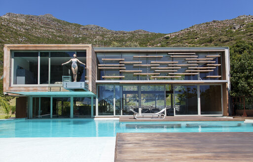 Woman on balcony over swimming pool - CAIF04411