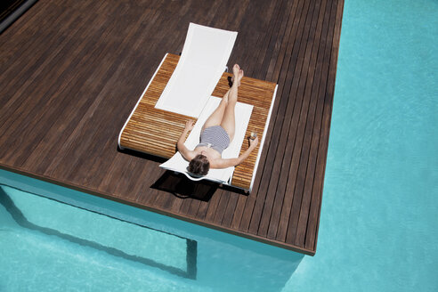 Woman sunbathing at poolside - CAIF04420