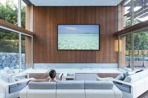 Woman watching large flat screen TV in modern living room - CAIF04423