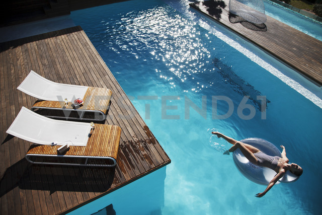 Woman floating on inflatable ring in luxury swimming pool - CAIF04426