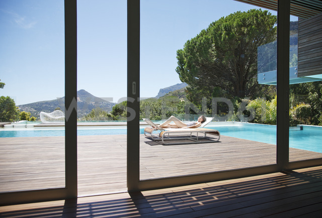 Woman sunbathing on lounge chair next to luxury swimming pool with mountain view - CAIF04429 - Astro-O/Westend61