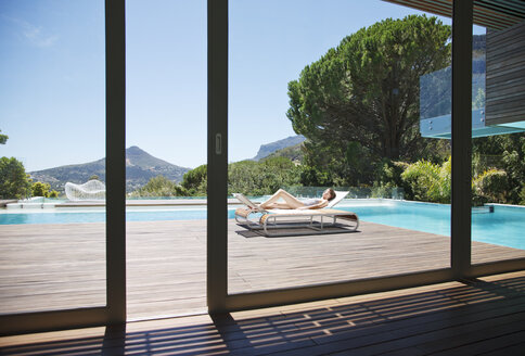 Woman sunbathing on lounge chair next to luxury swimming pool with mountain view - CAIF04429