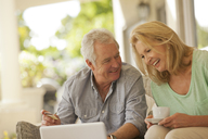 Smiling couple drinking coffee and shopping online on patio - CAIF04444