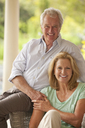 Portrait of smiling couple holding hands on patio - CAIF04453