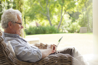 Senior man using digital tablet in wicker armchair on porch - CAIF04456