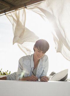 Smiling woman writing on sunny patio - CAIF04462