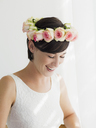 Smiling bride wearing rose wreath on head - CAIF04483