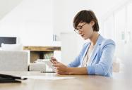 Woman using digital tablet at table - CAIF04492
