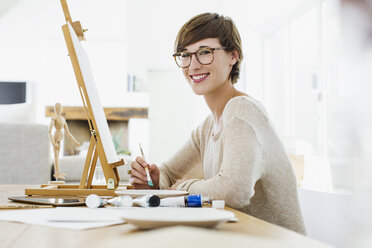 Portrait of smiling woman painting at easel on table - CAIF04495