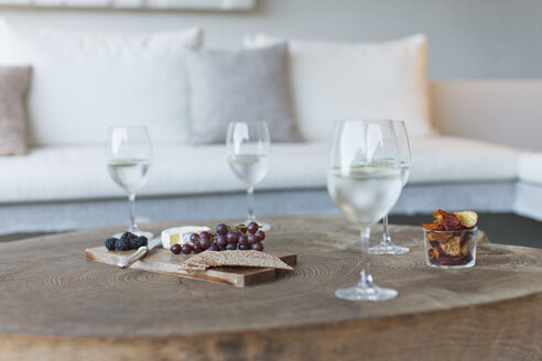Wine and cheese on wooden coffee table - CAIF04519