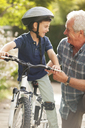 Grandfather teaching grandson to ride bicycle - CAIF04540