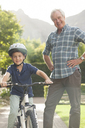 Older man teaching grandson to ride bicycle - CAIF04552