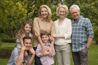 Portrait of multi-generation family smiling outdoors - CAIF04555