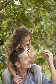 Father carrying daughter on shoulders outdoors - CAIF04567
