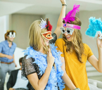 Women wearing decorative glasses and headpieces at party - CAIF04579