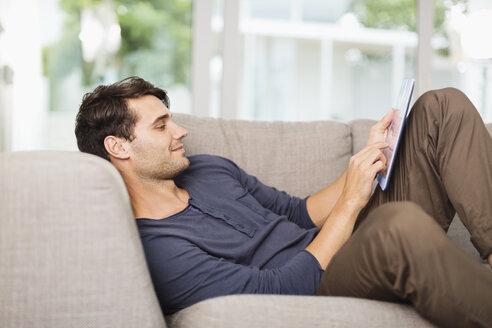 Man using digital tablet on sofa - CAIF04585
